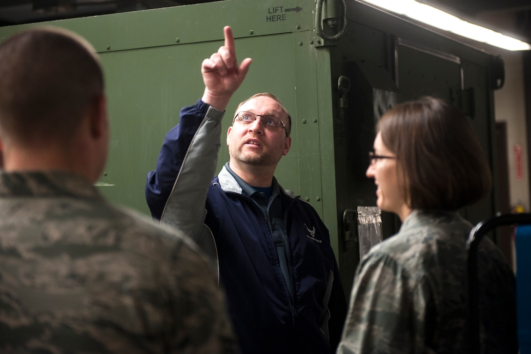 Ryan Fictum, a senior occupational health and safety specialist, points to a ventilation system as bioenvironmental Airmen look on during a health-risk assessment at Moody Air Force Base, Ga., March 25, 2013. During health-risk assessments, bioenvironmental Airmen look for possible hazards to help ensure short-term and long-term safety of Airmen. (U.S. Air Force photo by Senior Airman Jarrod Grammel/Released)