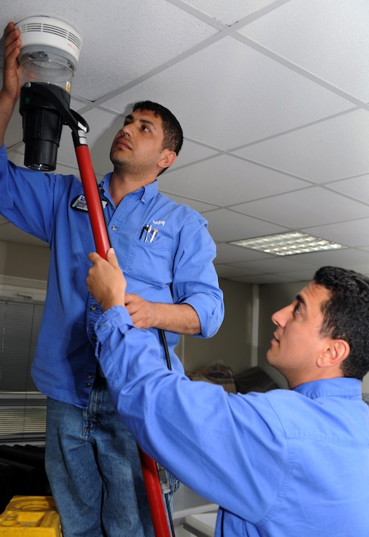Ugur Uyar  (left) and Mehmet Sami Sevinc, both Vinnell-Brown and Root fire alarm technicians assigned to the 39th Civil Engineer Squadron, activate a fire alarm April 4, 2013, at Incirlik Air Base, Turkey. The VBR contractors are crucial to the Patriot Mission, ensuring incoming NATO service members have sufficient, safe living accommodations at Incirlik's contingency lodging area. (U.S. Air Force photo by Staff Sgt. Marissa Tucker/Released)