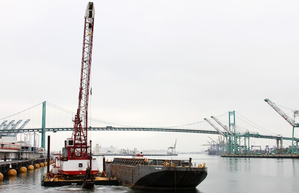 """A crane lifts the last bucketfull of material from the Port of Los Angeles main channel April 3, marking the end of the Corps' 10-year project.  The dredging project removed 15 million cubic yards of material in total, deepening the channel to a depth of 53 feet that will allow passage of """"post-Panamax"""" ships."""