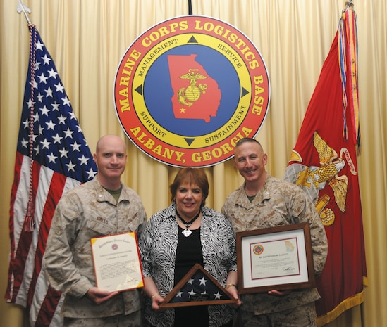 Catherine Salucci, traffic manager, Distribution Management Office, center, showcases her awards during her retirement March 21 with Col. Don Davis, commanding officer, MCLB Albany, right, and Lt. Col. Daniel Bates, executive officer, MCLB Albany.