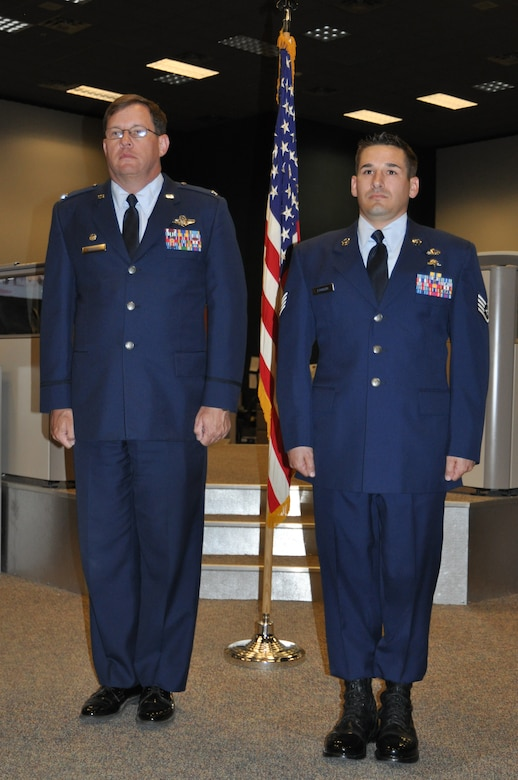 Col. James Bortree, 612th Air and Space Operations Center commander, stands at attention with Staff Sgt. Staff Sgt. Darren C. Fackler, 612th AOC Survival, Evasion, Resistance and Escape specialist, during Fackler's Purple Heart recognition ceremony at Davis-Monthan AFB, Ariz., April 4. (USAF photo by Master Sgt. Kelly Ogden/Released).