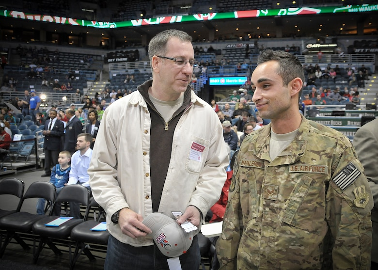 """Senior Airman Jefferson Harkleroad, an Air Force electrician serving in the Civil Engineering Squadron at Milwaukee's 128th Air Refueling Wing, stands courtside at the BMO Harris Bradley Center in Milwaukee with his father, Senior Master Sgt. Phil Harkleroad, Wed., April 3, 2013. Harkleroad, who had recently returned from a deployment to Afghanistan, was honored by the Milwaukee Bucks and Waukesha Metal as part of their """"Hardwood Homecoming"""" program and presented the official game ball the team captains prior to the start of the game.  (Air National Guard Photo by 1st Lt. Nathan Wallin / Released)"""
