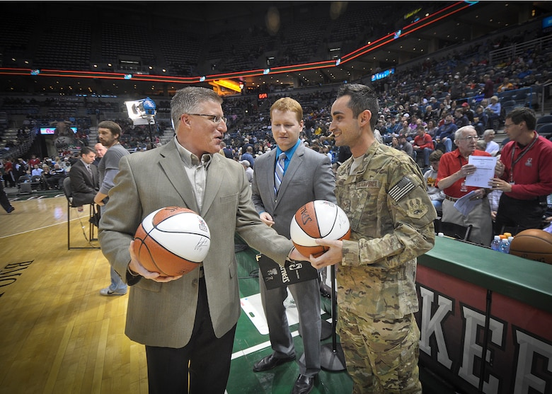 """Michael Steger of Waukesha Metal hands an autographed souvenir basketball to Senior Airman Jefferson Harkleroad following a recognition ceremony at center court of the BMO Harris Bradley Center in Milwaukee, Wed., April 3, 2013. Harkleroad, an electrician serving in the Civil Engineering Squadron of Milwaukee's 128th Air Refueling Wing, recently returned from a deployment to Afghanistan and was recognized prior to the Bucks game against the Minnesota Timberwolves as part of the """"Hardwood Homecoming"""" program. (Air National Guard Photo by 1st Lt. Nathan Wallin / Released)"""