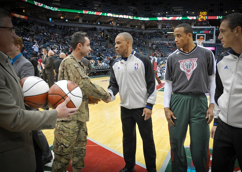 """Senior Airman Jefferson Harkleroad, an Air Force electrician serving in the Civil Engineering Squadron at Milwaukee's 128th Air Refueling Wing, shakes hands with an NBA referee at center court of the BMO Harris Bradley Center in Milwaukee Wed., April 3, 2013.  Harkleroad, who had recently returned from a deployment to Afghanistan, was recognized prior to the Bucks game against the Minnesota Timberwolves as part of the """"Hardwood Homecoming"""" program. (Air National Guard Photo by 1st Lt. Nathan Wallin / Released)"""