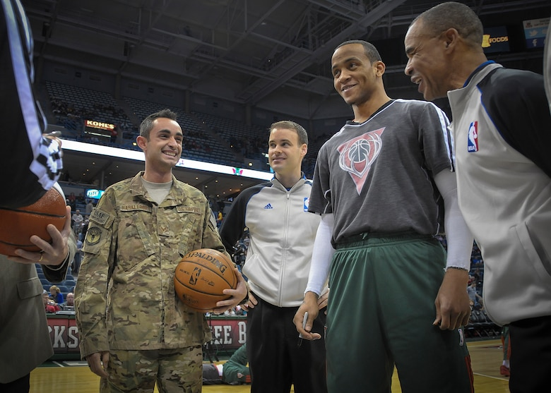 """Senior Airman Jefferson Harkleroad is all smiles at center court of the BMO Harris Bradley Center in Milwaukee Wed., April 3, 2013.   Harkleroad, an Air Force electrician serving in the Civil Engineering Squadron at Milwaukee's 128th Air Refueling Wing, was honored by the Milwaukee Bucks and Waukesha Metal as part of their """"Hardwood Homecoming"""" program. (Air National Guard Photo by 1st Lt. Nathan Wallin / Released)"""