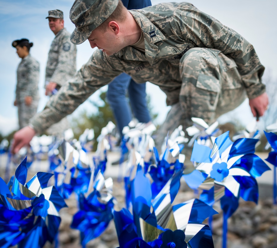 Capt. Steven Hyer plants a pinwheel near the main gate in recognition of Child Abuse Prevention Month April 1, 2013, at Mountain Home Air Force Base, Idaho. Stressful or traumatic childhood experiences have been linked to social, emotional or cognitive impairments in adults. Hyer is assigned to the 366th Medical Operations Squadron. (U.S. Air Force photo/Tech. Sgt. Samuel Morse)
