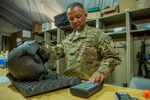 Senior Master Sgt. Vincent Aldama inspects an HGU-56/P aircrew flight helmet March 8, 2013, on Camp Bastion, Afghanistan. Aldama is responsible for flight equipment such as helmets, oxygen masks, parachutes, flotation devices, survival kits, night vision goggles, anti-G garments, aircrew eye and respiratory protective equipment and other types of aircrew flight equipment. Aldama is an aircrew flight equipment specialist deployed to the 26th Expeditionary Rescue Squadron. (U.S. Air Force photo/Tech. Sgt. Dennis J. Henry Jr.)