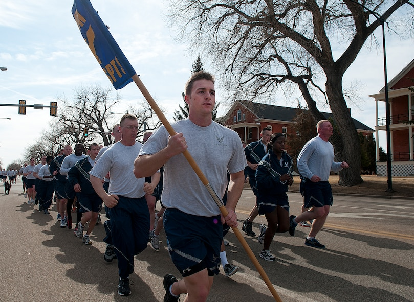 "Senior Airman Craig Eveland, 90th Security Support Squadron, carries his squadron's guidon as he leads them down Randall Avenue on F. E. Warren Air Force Base March 29. Eveland and his fellow Airmen were taking part in the 90th Security Forces Group two-mile ""pride run."" (U.S. Air Force photo by R.J. Oriez)"