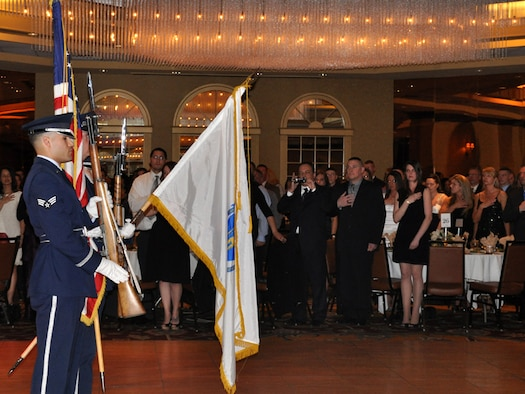 Approximately 400 members and their families stand with hands over their hearts while the national anthem is sung and the honor guard stands at attention during the annual awards banquet. Members of the 104th Fighter Wing celebrated the accomplishments of their peers at the 39th annual awards banquet held at the Sheraton Hotel, Springfield, Mass., April 6, 2013. (Air National Guard photo by Maj. Mary Harrington)