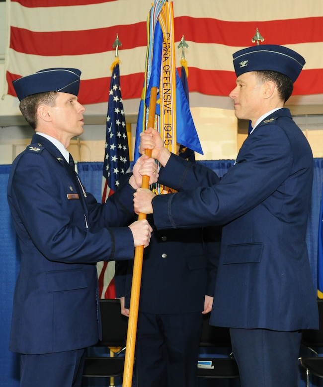 New York Air National Guard Col. Michael Comella (right), incoming commander of the 152nd Air Operations Group, accepts the guidon from Col. Greg Semmel,174th Attack Wing Commander, during a Change of Command Ceremony held at Hancock Field Air National Guard Base, Syacuse, New York on April 6, 2013. (New York Air National Guard photo by Tech. Sgt. Justin A. Huett/Released)