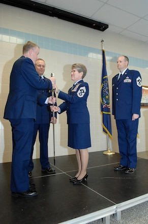 Relinquishing her position as the top enlisted service member in the Utah Air National Guard, State Command Chief Master Sgt. Denise Rager passes the sword to the Director of the Utah National Guard's Joint Staff, Brig. Gen. Kenneth L. Gammon, during a ceremony at the Utah ANG base, April 6. In the passing-of-the-sword ceremony, the sword represents the duties and responsibilities of the State Command Chief Position. Chief Master Sgt. Michael Edwards then assumed position as the new State Command Chief. (U.S. Air Force photo by Senior Master Sgt. Gary Rihn)(RELEASED)