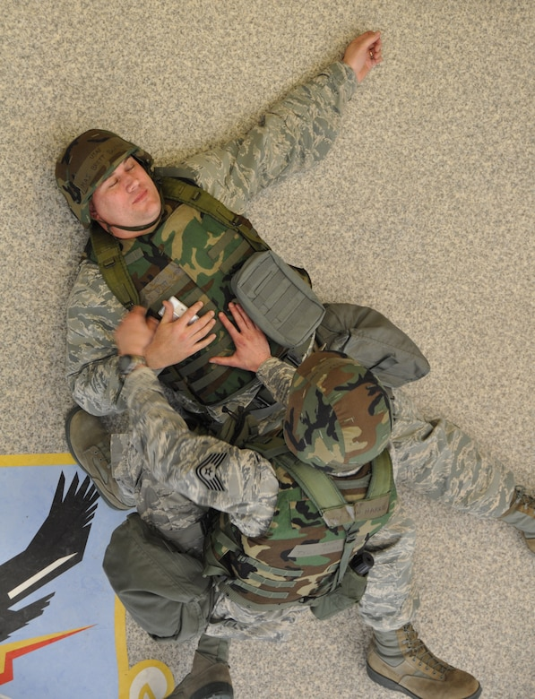 Tech. Sgt. John Harris applies self aid buddy care techniques to Maj. Brett Bakner's simulated injuries during Polar Force 13-3. Harris and Bakner are both assigned to the 477th FG, Alaska's only Reserve unit. The 477th FG along with the Air National Guard 176th Wing and active duty 3rd Wing and 673rd Air Base Wing participated  in the operational readiness exercise designed to test the unit's ability to deploy. (U.S. Air Force Reserve/Tech. Sgt. Dana Rosso)