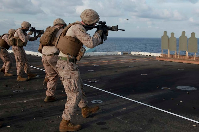 Marines with Kilo Company, Battalion Landing Team 3/5, 15th Marine Expeditionary Unit, fire at targets during a range held on the flight deck of USS Peleliu, April 6. Fifty Marines of Kilo Company, BLT 3/5, 15th MEU conducted the combat marksmanship program to keep their skills razor sharp. The 15th MEU is comprised of approximately 2,400 Marines and sailors and is deployed as part of the Peleliu Amphibious Ready Group. Together, they provide a forward-deployed, flexible sea-based Marine Air Ground Task Force capable of conducting a wide variety of operations ranging from humanitarian aid to combat. (U.S. Marine Corps photo by Cpl. John Robbart III)