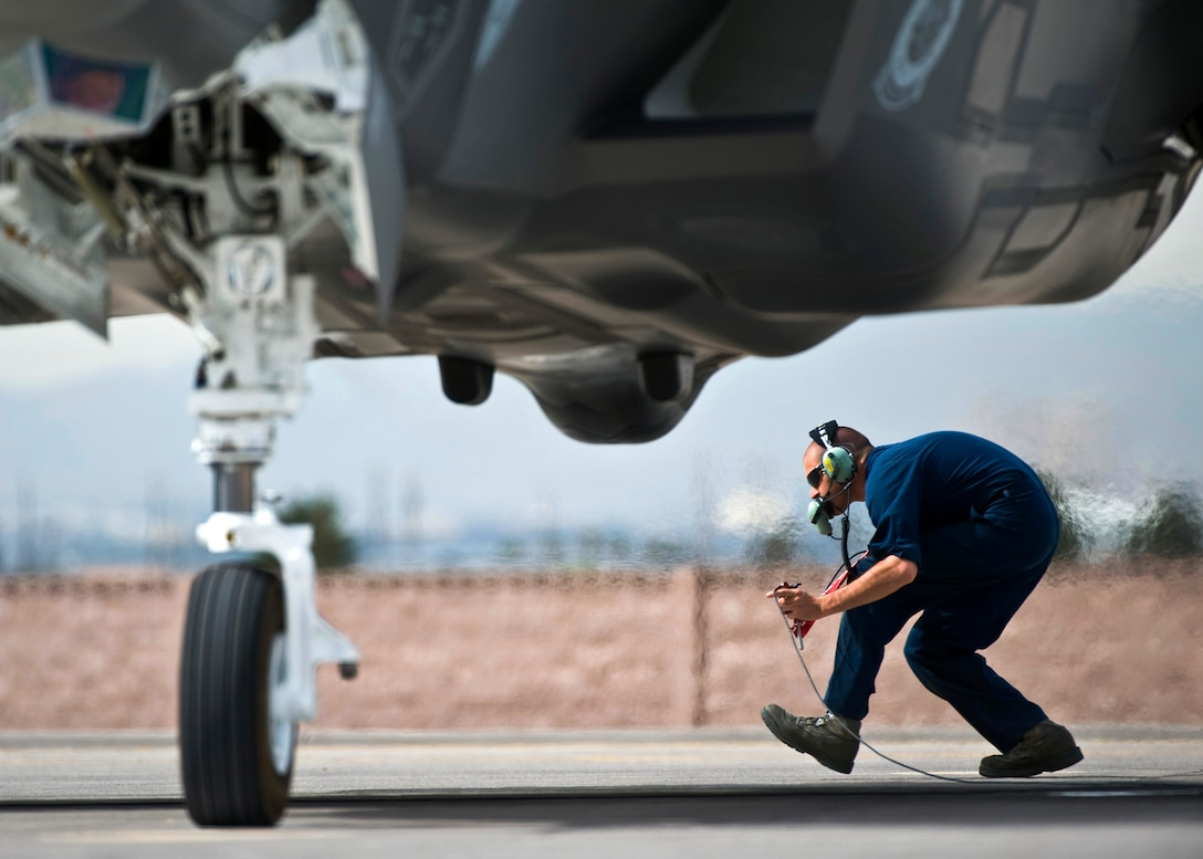 U.S. Air Force Senior Airman Alexander Orchard, 57th Aircraft Maintenance Squadron crew chief, crouches underneath the exhaust of an F-35A Lightning II before a training mission April 4, 2013, at Nellis Air Force Base, Nev. The F-35A is assigned to the 422nd Test and Evaluation Squadron and maintained by the 57th AMXS Lightning Aircraft Maintenance Unit. (U.S. Air Force photo/Senior Airman Brett Clashman)