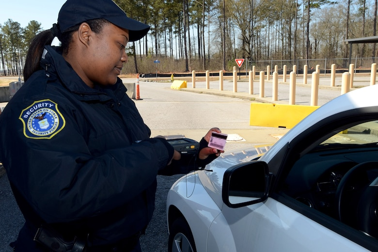 Ms. Veronica Dennis, security forces personnel with the 169th Security Forces Squadron at McEntire Joint National Guard Base, S.C., checks ID cards at the main gate entrance using the Defense Biometric Identification System scanner, March 28, 2013. (National Guard photo by Tech. Sgt. Caycee Watson/Released)