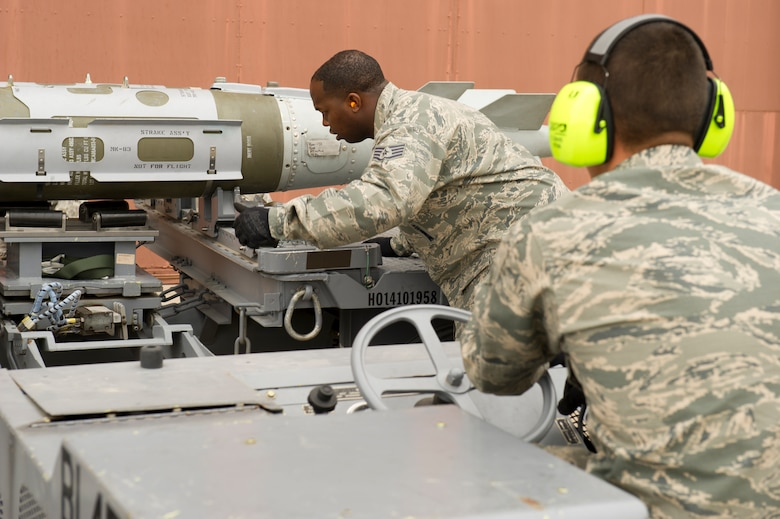 Staff Sgt. Kevin Hagans, 49th Aircraft Maintenance Squadron load team member, directs Senior Airman Chad Davis, 49th Aircraft Maintenance Squadron load team member, while preparing to load a missile onto an F-22 Raptor aircraft during the quarterly load-crew competition at Holloman Air Force Base, N.M., April 5. The F-22 load-crew competed in the load-crew competition to have their skills evaluated alongside the MQ-9 Reaper aircraft and German Air Force load-crews. For the competition, points are awarded during the weapons loading, tool kit inspection, and uniform inspection. (U.S. Air Force photo by Airman 1st Class Michael Shoemaker/Released)