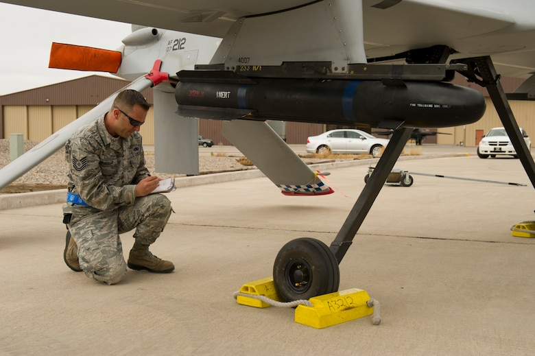 Technical Sgt. Travis Wheeler, 849th Aircraft Maintenance Squadron load team member, reviews his checklist on an MQ-1 Predator aircraft during the load-crew competition at Holloman Air Force Base, N.M., April 5. Load-crew competitions are held on a quarterly basis and are used to help build morale through friendly competition. (U.S. Air Force photo by Airman 1st Class Michael Shoemaker/Released)
