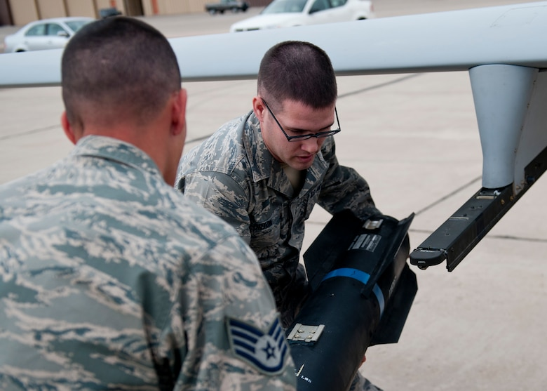 Staff Sgt. Michal Game and Senior Airman Randall Orton, both 849th Aircraft Maintenance Squadron, remove an inert missile from an MQ-1 Predator aircraft during a quarterly load-crew competition at Holloman Air Force Base, N.M., April 5. The 849th AMXS pitted two MQ-1 load-crews against each other for the first time to evaluate who could prepare the aircraft for combat the quickest and with the fewest procedural errors. (U.S. Air Force photo by Airman 1st Class Daniel E. Liddicoet/Released)