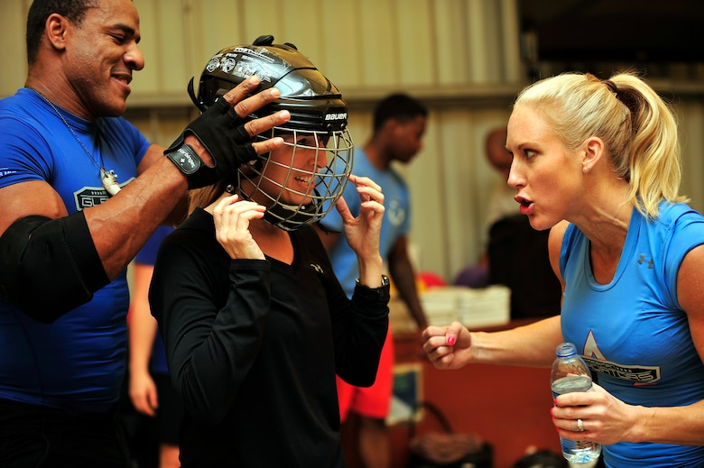 """American Gladiators, Alex """"Militia"""" Castro and Beth """"Venom"""" Horn, prepare U.S. Air Force Col. Laura Lenderman, 380th Air Expeditionary Wing vice commander, for the Joust competition at an undisclosed location in Southwest Asia April 6, 2013. The Gladiators and Billy Blanks visited several bases in Southwest Asia during an Armed Forces Entertainment Fitness Tour. (U.S. Air Force photo by Tech. Sgt. Christina M. Styer/Released)"""