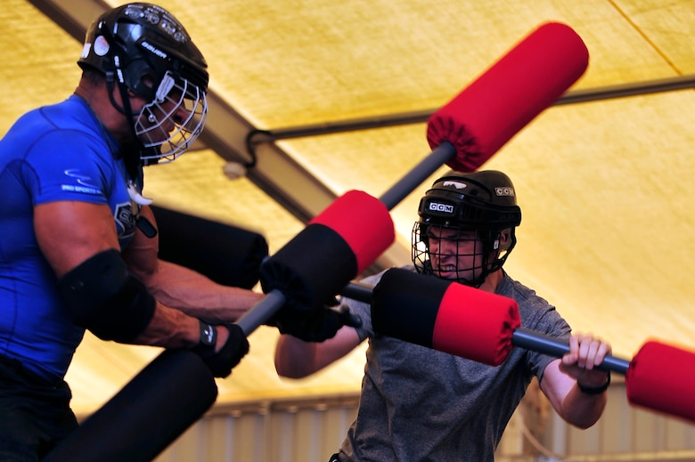 """U.S. Air Force Staff Sgt. Josef Miller, 380th Expeditionary Civil Engineer Squadron explosive ordnance disposal technician, deployed from Andersen Air Force Base, Guam, competes against American Gladiator, Alex """"Militia"""" Castro, during the Joust competition at an undisclosed location in Southwest Asia April 6, 2013. The Gladiators and Billy Blanks visited several bases in Southwest Asia during an Armed Forces Entertainment Fitness Tour. (U.S. Air Force photo by Tech. Sgt. Christina M. Styer/Released)"""