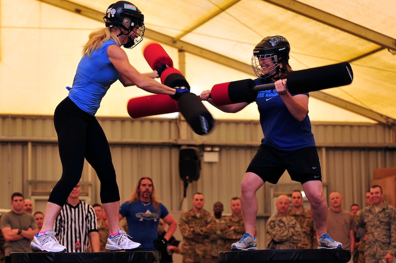 """U.S. Air Force Staff Sgt. Tricia Briggs, 380th Expeditionary Operations Support Squadron weather forecaster, deployed from Luke Air Force Base, Ariz., competes against American Gladiator, Beth """"Venom"""" Horn, during the Joust competition at an undisclosed location in Southwest Asia April 6, 2013. The Gladiators and Billy Blanks visited several bases in Southwest Asia during an Armed Forces Entertainment Fitness Tour. (U.S. Air Force photo by Tech. Sgt. Christina M. Styer/Released)"""