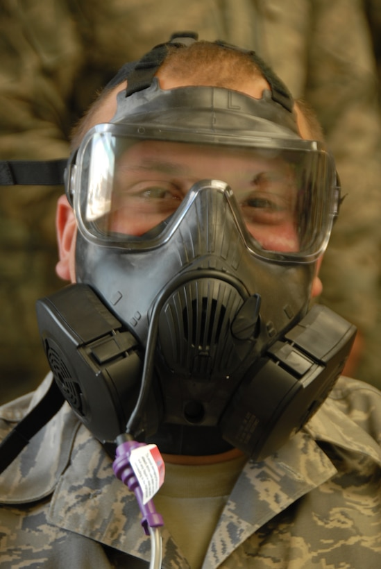 Senior Airman David Nelson, 115th Fighter Wing fuel shop, tests his gas mask for a good seal at the Credit Union building on Truax Field on April 7. Nelson used different breathing techniques and moved his head various directions to ensure his mask had a good seal throughout the testing. Airman at the 115th Fighter Wing just received the M50 gas masks and will all be required to accomplish the fit-tests on their masks. (Air National Guard photo by Andrea F. Liechti)