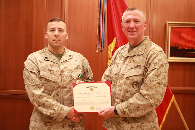 Lt. Gen. Steven A. Hummer, commander of Marine Forces Reserve and Marine Forces North, poses with Sgt. Adam K. Smith after presenting  him with a citation for his Navy and Marine Corps Commendation Medal at the Marine Corps Support Facility New Orleans, April 8, 2013. Smith, the repairable issue point chief for MARFORRES G4 (logistics and services), was awarded the medal after he was selected as the MARFORRES 2012 Marine of the Year (active component).
