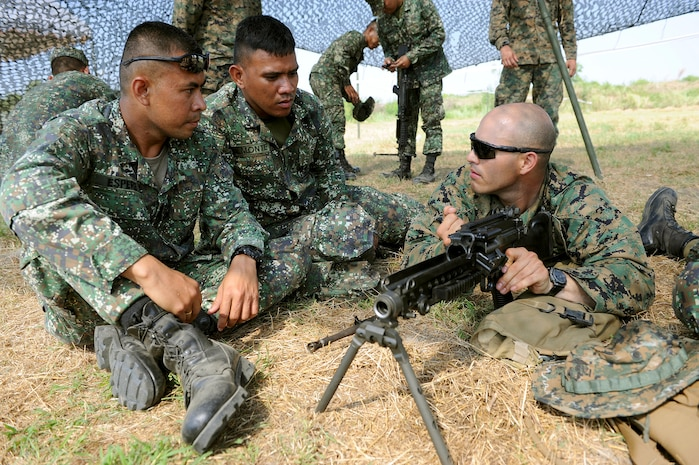 From left to right: Philippine Marine Cpl. Milky Espere and Cpl. Raymond Almonte, with the Philippine Transportation and Maintenance, observe U.S. Marine Lance Cpl. Adrian Sandoval, with Combat Logistics Regiment 35, 3rd Marine Logistics Group, III Marine Expeditionary Force, as he demonstrates how to disassemble a M240 machine gun April 5 during a bilateral subject matter expert exchange at a field training exercise in support of Balikatan 2013 at Camp O'Donnell, Philippines. BK13 is an annual bilateral exercise between the Armed Forces of the Philippines and U.S. forces to enhance interoperability, improve military-to-military relations, and refine combined and joint-force planning in response to humanitarian assistance and disaster relief operations.