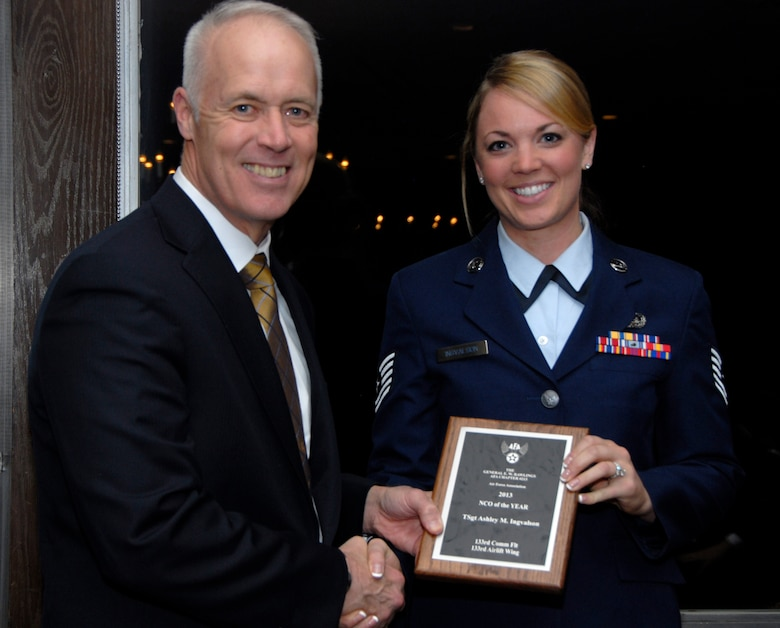 Tech. Sgt. Ashley Ingvalson, 133rd Communications Flight, receives an award from Retired U.S. Air Force Lt. Gen. Richard Newton, Executive Vice President of the Air Force Association in St. Paul, Minn., Apr. 5, 2013. Ingvalson is being honored for being the 133rd Airlift Wing NCO of the Year award during the Air Force Association's Annual Awards Dinner. (U.S. Air Force photo by Airman 1st Class Kari Giles /Released)