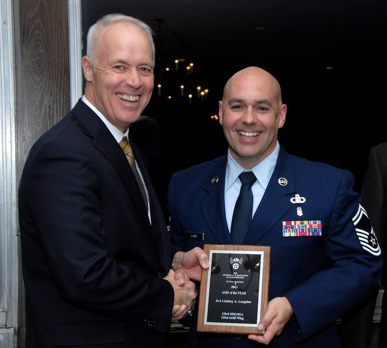 Senior Master Sgt. Duke Lang, 133rd Medical Group, accepts an award for Senior Airman Lindsey Longtine from Retired U.S. Air Force Lt. Gen. Richard Newton, Executive Vice President of the Air Force Association in St. Paul, Minn., Apr. 5, 2013. Longtine is being honored during the Air Force Association's Annual Awards Dinner for being the 133rd Airlift Wing Outstanding Airman of the Year. (U.S. Air Force photo by Airman 1st Class Kari Giles /Released)