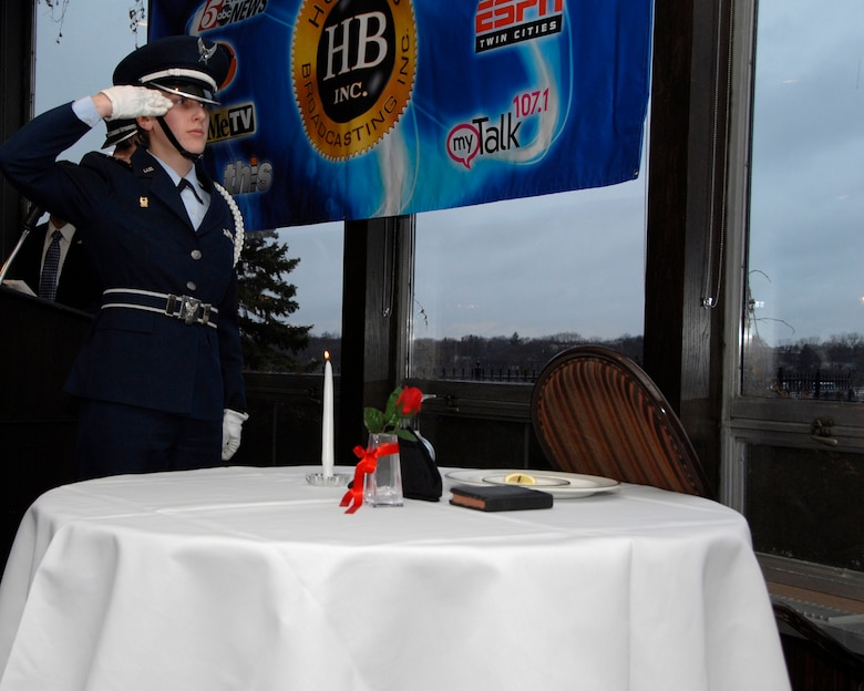 Cadet LeAnne Pratt, University of St. Thomas ROTC Detachment 410, salutes the lit candle glass during The Missing Man Ceremony at the Air Force Association's Annual Awards Dinner in St. Paul, Minn., Apr. 5, 2013. This candle is reminiscent of the light of hope that lives in our hearts to illuminate their way home, away from their captors, to the open arms of a grateful nation.  (U.S. Air Force photo by Airman 1st Class Kari Giles/Released)
