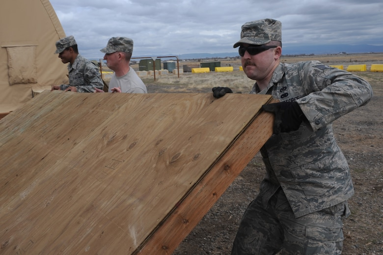 U.S. Air Force Airman 1st Class Nathan Coleman, Staff Sgt. Chris Carpenter and Staff Sgt. Kyle McCloskey, 366th Civil Engineer Squadron structures technicians, put in place a revetment wall at a simulated deployed location, Mountain Home Air Force Base, Idaho, April 1, 2013. Revetments are essential in protecting base assets and personnel down range. (U.S. Air Force photo/Staff Sgt. Roy Lynch) (Released)