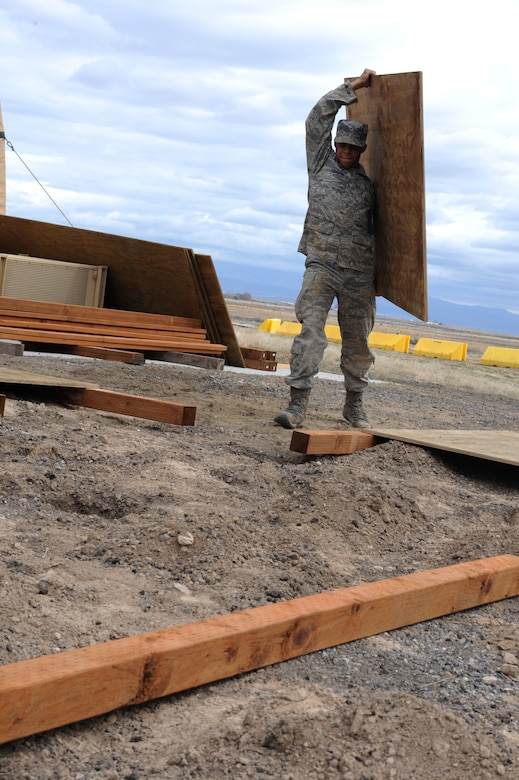 U.S. Air Force Airman 1st Class Nathan Coleman, 366th Civil Engineer Squadron structures journeyman, carries plywood at a simulated deployed location, Mountain Home Air Force Base, Idaho, April 1, 2013. Revetment is a barrier protecting military assets and is only limited to the ingenuity of the person doing the construction. (U.S. Air Force photo/Staff Sgt. Roy Lynch) (Released)