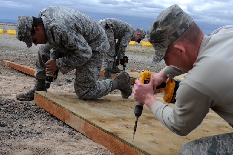 U.S. Air Force Airman 1st Class Nathan Coleman, Staff Sgt. Kyle McCloskey and Staff Sgt. Chris Carpenter, 366th Civil Engineer Squadron structures technicians, prepare a revetment wall at a simulated deployed location, Mountain Home Air Force Base, Idaho, April 1, 2013. The 366th Fighter Wing is required to protect military assets in the upcoming Certified Readiness Exercise and this revetment meets that requirement. (U.S. Air Force photo/Staff Sgt. Roy Lynch) (Released)