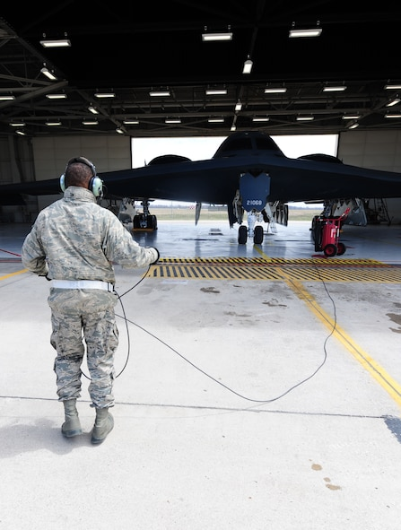 Airman 1st Class Steven McCray, 13th Aircraft Maintenance Unit B-2 Spirit crew chief, speaks to his pilots with a communications cord during a pre-flight inspection at Whiteman Air Force Base, April 5, 2013. Pilots and crew chiefs conduct pre-flight inspections to ensure all components of the jet are mission-capable before flight. (U.S. Air Force photo by Staff Sgt. Nick Wilson/Released)
