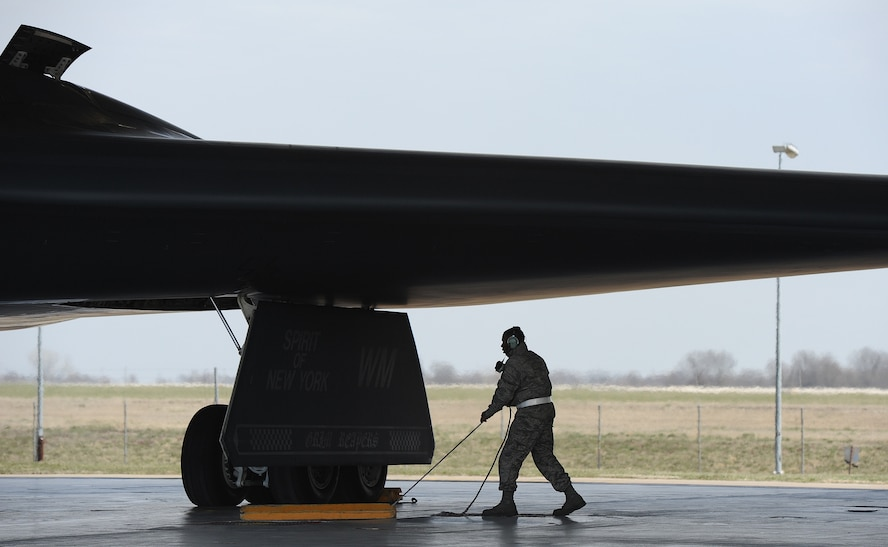 Airman 1st Class Steven McCray, 13th Aircraft Maintenance Unit B-2 Spirit crew chief, removes chalks before performing launch operations on a B-2 Spirit, Whiteman Air Force Base, April 5, 2013. McCray is 23 years old and has been a crew chief in the Air Force for two years. (U.S. Air Force photo by Staff Sgt. Nick Wilson/Released)