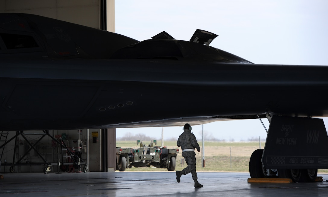 Airman 1st Class Steven McCray, 13th Aircraft Maintenance Unit B-2 Spirit crew chief, runs to remove wheel chalks before performing launch operations on a B-2 Spirit at Whiteman Air Force Base, April 5, 2013. McCray is 23 years old and has been a crew chief in the Air Force for two years. (U.S. Air Force photo by Staff Sgt. Nick Wilson/Released)