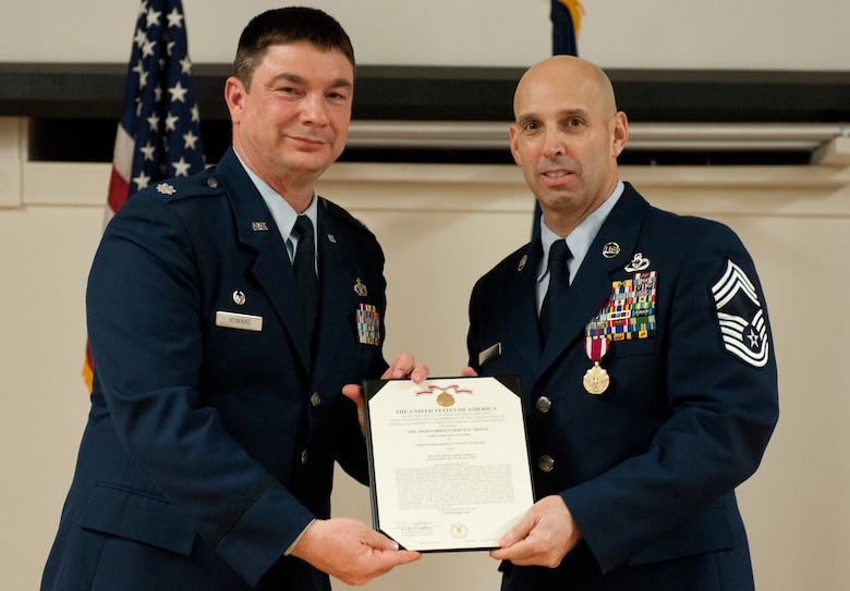 Chief Master Sgt. Steven Peters (right) is presented with a Meritorious Service Medal by Lt. Col. Phil Howard, commander of the 123rd Civil Engineer Squadron, during a retirement ceremony held in Peters' honor at the Kentucky Air National Guard Base in Louisville, Ky., on Feb. 2, 2013. Peters, the squadron's chief of operations, served in the active-duty Air Force and Air National Guard for three decades. (U.S. Air Force photo by Airman Joshua Horton)