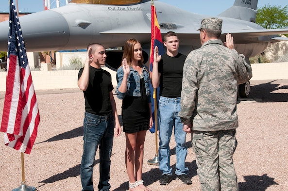 With an F-16 Fighting Falcon in the background, the Aubuchon triplets take the oath of enlistment from Col. Mick McGuire at the 162nd Fighter Wing's air park, April 6 in Tucson, Ariz. Christopher, Adrianna and Andrew turned 18 Mar. 31st, 2013, and are scheduled to attend basic training this August.  (U.S. Air Force photo by Master Sgt. David Neve/Released)
