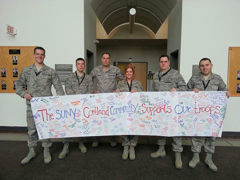 New York Air National Guard Senior Airman Zach Taillie (left) and fellow airmen of the 174th Attack Wing's Command Post section pose with the SUNY Cortland American Red Cross club banner at Hancock Field Air National Guard Base, Syracuse, New York. Senior Airman Taillie was recently selected to serve as Chair of the Armed Forces Committee of the Red Cross chapter. The banner is filled with signatures of students from SUNY Cortland. (Photo by New York Air National Guard Tech. Sgt. Philip Benjamin/Released)