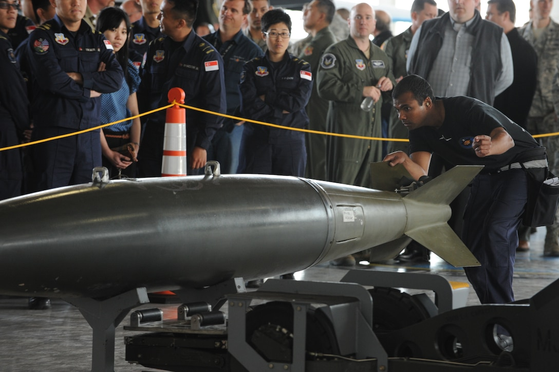 A Republic of Singapore Air Force service member inspects a weapon before loading it on to an F-15E Strike Eagle during a weapons load competition, April 5, 2013, at Mountain Home Air Force Base, Idaho. Each team worked together to efficiently and accurately load weaponry in the 15-minute time-frame. (U.S. Air Force Photo/Airman 1st Class Malissa Lott)