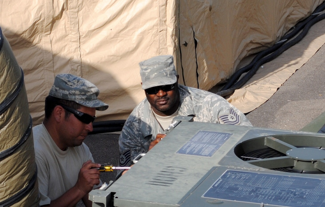 Master Sgt. Alex Torres, left, and Tech. Sgt. Johnny Gordon of the 55th Combat Communications Squadron, Robins Air Force Base, Ga., perform maintenance on a communications equipment cooling unit in support of African Lion 2013 in Morocco on April 9. African Lion is an annually scheduled, bilateral U.S. and Moroccan sponsored exercise designed to improve interoperability and mutual understanding of each nation's tactics, techniques and procedures. This year, the 55th CBCS was selected to provide communications support for the exercise. (U.S. Air Force photo by SrA. Will Toussaint)