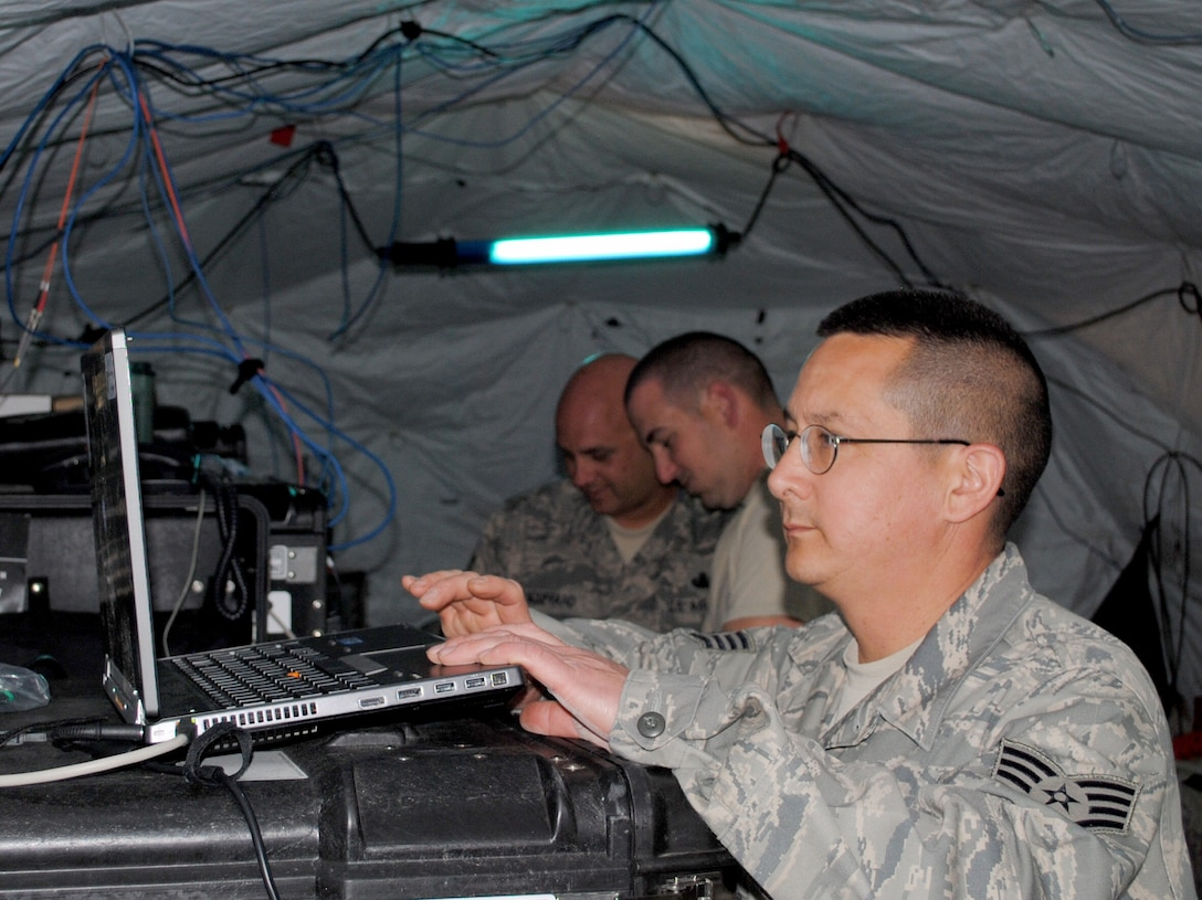 Staff Sgt. Johnny Linch, foreground, double checks settings for network routing while Master Sgt. Lou Bouffard and Staff Sgt. Michael Russano, all of the 55th Combat Communications Squadron, Robins Air Force Base, Ga., configure settings on network servers in support of African Lion 2013 in Morocco on April 9. African Lion is an annually scheduled, bilateral U.S. and Moroccan sponsored exercise designed to improve interoperability and mutual understanding of each nation's tactics, techniques and procedures. This year, the 55th CBCS was selected to provide communications support for the exercise. (U.S. Air Force photo/SrA. Will Toussaint)