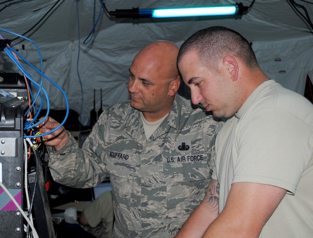 Master Sgt. Lou Bouffard and Staff Sgt. Michael Russano of the 55th Combat Communications Squadron, Robins Air Force Base, Ga., configure settings on network servers in support of African Lion 2013 in Morocco on April 9. African Lion is an annually scheduled, bilateral U.S. and Moroccan sponsored exercise designed to improve interoperability and mutual understanding of each nation's tactics, techniques and procedures. This year, the 55th CBCS was selected to provide communications support for the exercise. (U.S. Air Force photo/SrA. Will Toussaint)