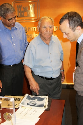 Holocaust survivor Albert Rosa shows employees his photos and other items he brought for his visit to talk about his experience in the concentration camps April 9.