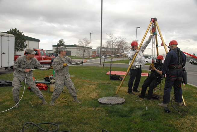 Firefighters with the 151st Air Refueling Wing participate in a confined space emergency rescue exercise April 11, 2013.  A mannequin lowered into a manhole served as a victim that Staff Sgt. Leo Jensen and Staff Sgt. Thomas Beck rescued.  Training exercises like this occur annually, allowing Guardsmen the chance to keep their abilities up to date, and to be prepared for any emergency.  (U.S. Air Force Photo by A1C Emily Hulse/Released)