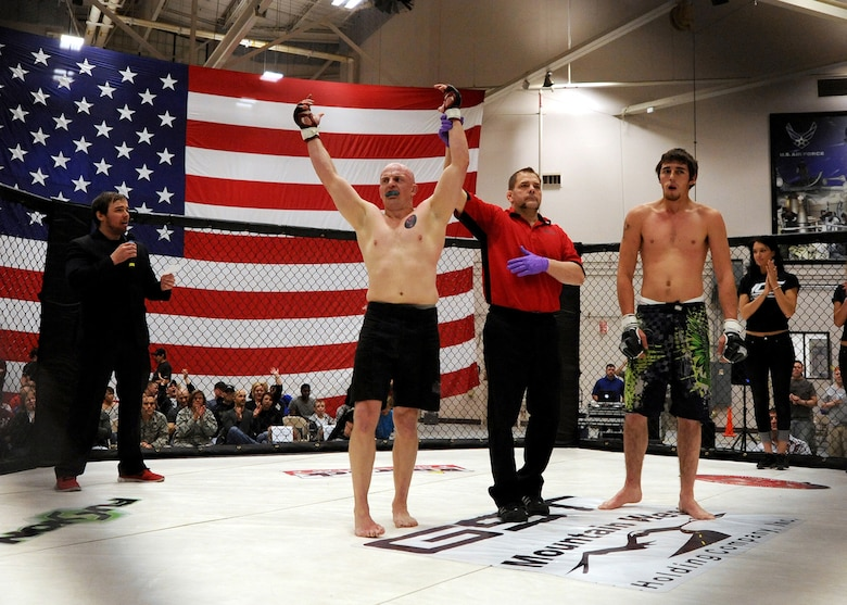 Mixed Martial Artist Travis Rourke's hand is raised by referee Bret Hamlin after Rourke's victory April 5 at Malmstrom Air Force Base. Rourke was a former Airman once assigned to Malmstrom. (U.S. Air Force photo/Staff Sgt. R.J. Biermann)