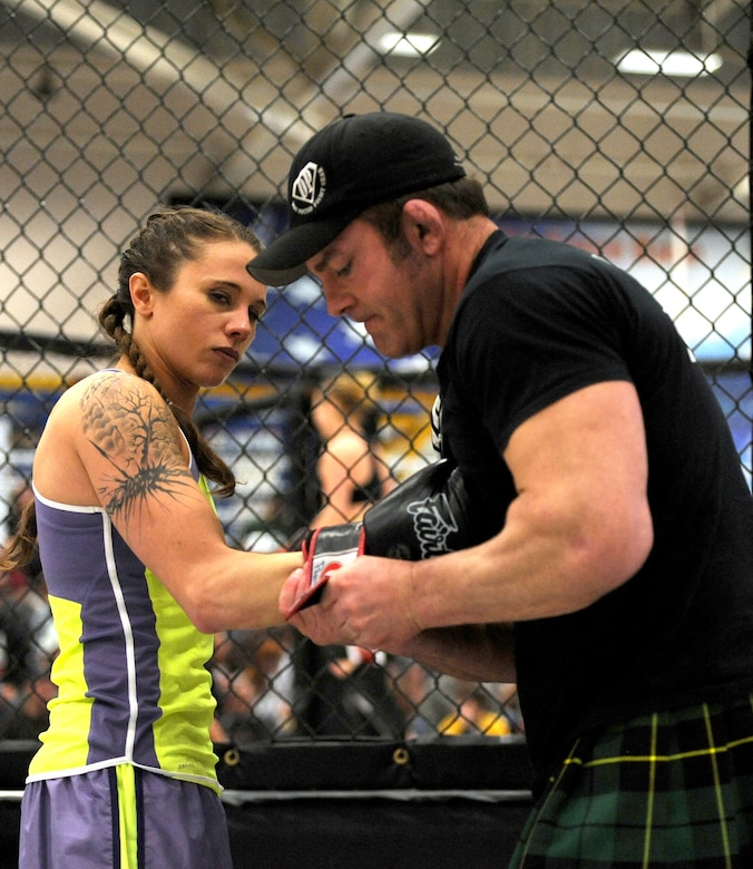 Coach Matt Powers, helps his kickboxer, Elisha Helsper, put her gloves on before entering the octagon to face fellow kickboxer, Aerial Beck, during the second of six fights at 221 Industries' first-ever Fight For the Troops event at Malmstrom Air Force Base, Mont., on April 5. Beck won the matchup by split decision. (U.S. Air Force photo/Staff Sgt. R.J. Biermann)