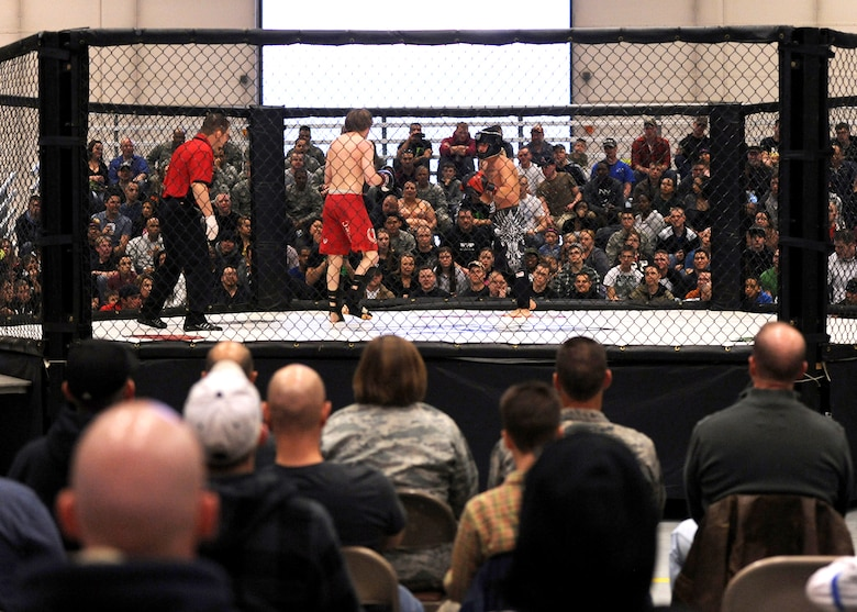 Two kickboxers circle around one another as referee, Bret Hamlin, looks on during 221 Industries' first-ever Fight For the Troops event at Malmstrom Air Force Base, Mont., on April 5. More than 1,100 Team Malmstrom members attended the event. (U.S. Air Force photo/Staff Sgt. R.J. Biermann)