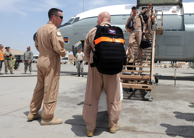 SOUTHWEST ASIA -  Lt. Col. Sean Coveney, 763rd Expeditionary Reconnaissance Squadron commander, congratulates  Airman 1st Class John Griffin, 763rd ERS aircrew, for being part of the crew which completed the squadron's 10,000th expeditionary sortie, April 10. The commander also gave each crewmember a coin to commemorate the milestone.  The squadron has been continuously deployed to the U.S. Central Command area of responsibility for nearly 23 years. (U.S. Air Force photo/Staff Sgt. Joel Mease)
